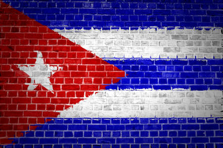 An image of the Cuba flag painted on a brick wall in an urban location photo