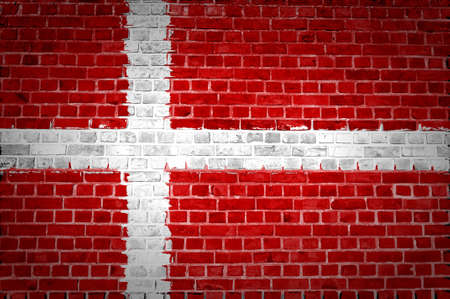 An image of the Denmark flag painted on a brick wall in an urban location