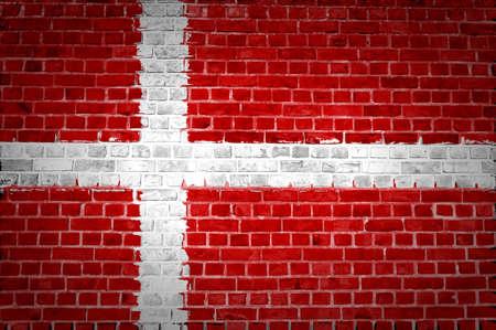 Een beeld van de Denemarken vlag geschilderd op een bakstenen muur in een stedelijke locatie