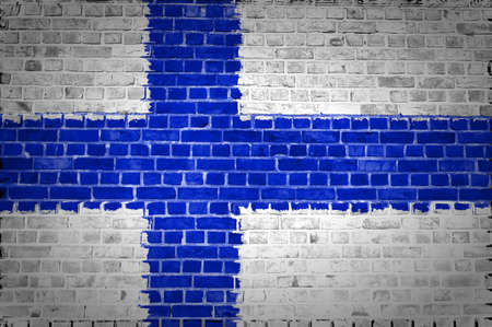 An image of the Finland flag painted on a brick wall in an urban location photo