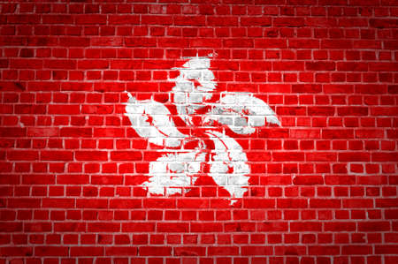 An image of the Hong Kong flag painted on a brick wall in an urban location photo