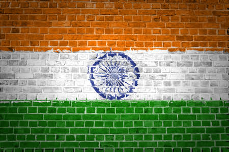 An image of the India flag painted on a brick wall in an urban location photo