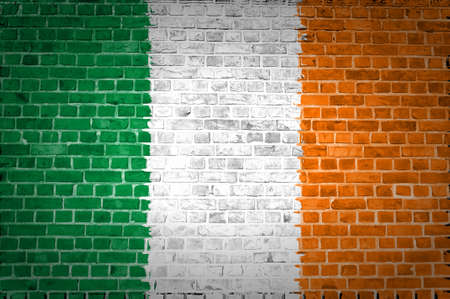 An image of the Ireland flag painted on a brick wall in an urban location photo