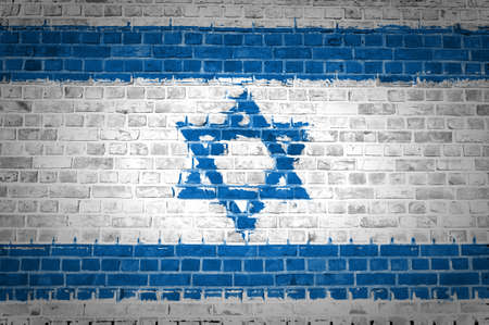 An image of the Israel flag painted on a brick wall in an urban location