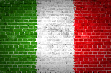 An image of the Italy flag painted on a brick wall in an urban location