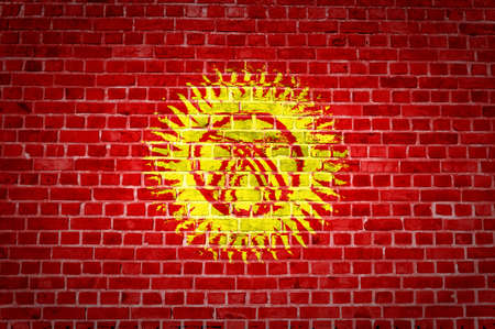 An image of the Kyrgyzstan flag painted on a brick wall in an urban location photo