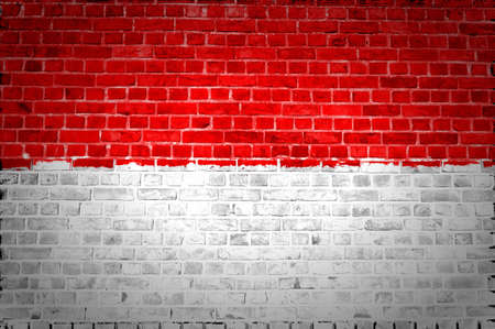 An image of the Monaco flag painted on a brick wall in an urban location photo