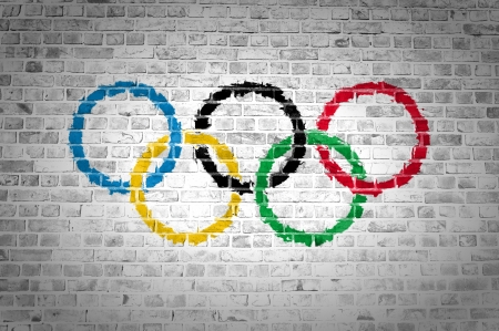 An image of the Olympic Movement flag painted on a brick wall in an urban location