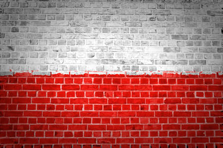 An image of the Poland flag painted on a brick wall in an urban location photo
