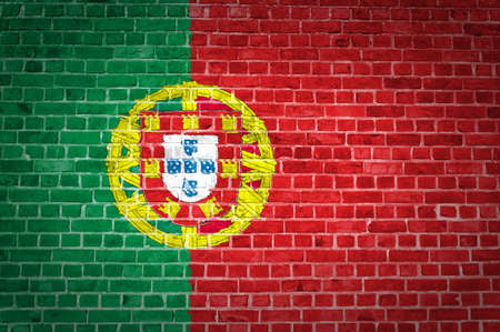 An image of the Portugal flag painted on a brick wall in an urban location photo