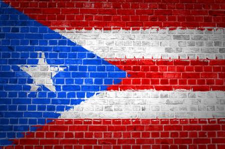 bandera de puerto rico: Una imagen de la bandera de Puerto Rico pintada en una pared de ladrillos en una ubicaci�n urbana