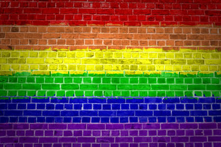 An image of the Rainbow flag painted on a brick wall in an urban location photo