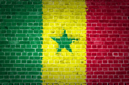 senegal: An image of the Senegal flag painted on a brick wall in an urban location