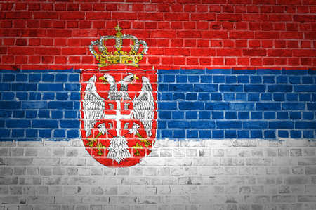 An image of the Serbia flag painted on a brick wall in an urban location photo