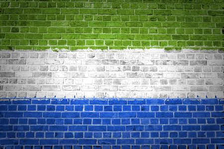 An image of the Sierra Leone flag painted on a brick wall in an urban location photo