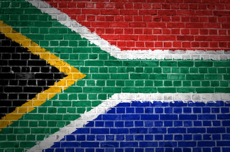 An image of the South Africa flag painted on a brick wall in an urban location
