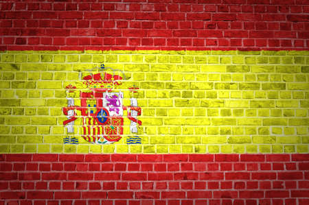 An image of the Spain flag painted on a brick wall in an urban location photo