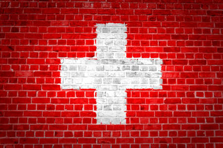 An image of the Switzerland flag painted on a brick wall in an urban location photo