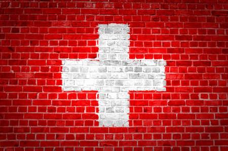 zwitserland vlag: Een beeld van de Zwitserland vlag geschilderd op een bakstenen muur in een stedelijke locatie Stockfoto