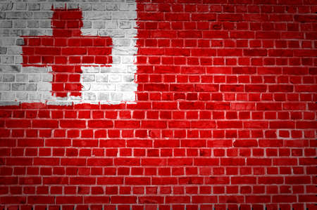 An image of the Tonga flag painted on a brick wall in an urban location