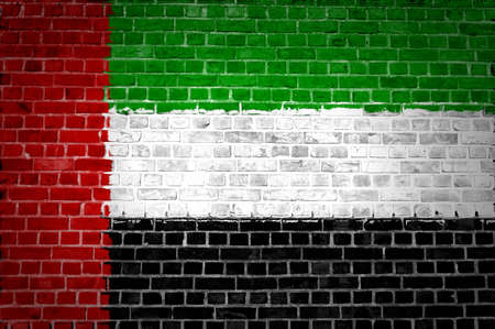 An image of the United Arab Emirates flag painted on a brick wall in an urban location photo