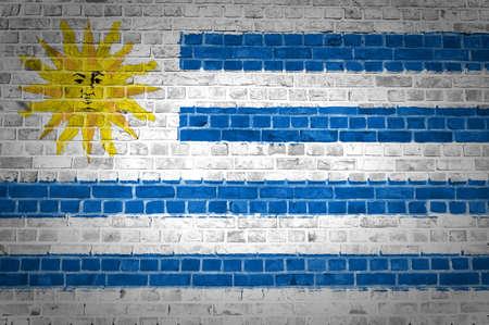 bandera de uruguay: Una imagen de la bandera de Uruguay pintada en una pared de ladrillos en una ubicación urbana