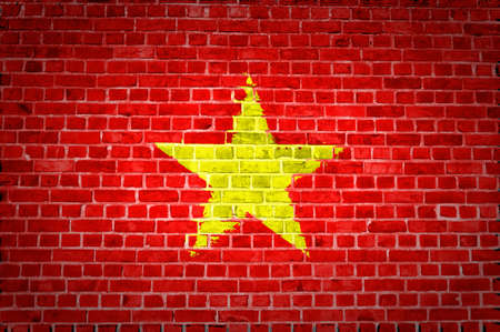 An image of the Vietnam flag painted on a brick wall in an urban location photo