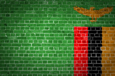 An image of the Zambia flag painted on a brick wall in an urban location