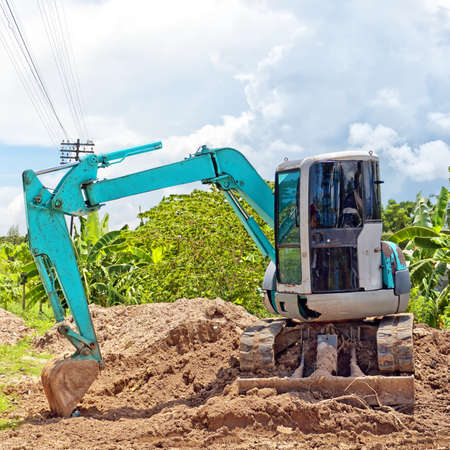 A small industrial digger moves earth at a building site. Imagens