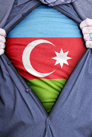 azerbaijanian: An Azerbaijanian businessman rips open his shirt and shows how patriotic he is by revealing his countries flag beneath printed on a t-shirt Stock Photo