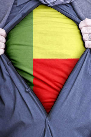 A Beninese businessman rips open his shirt and shows how patriotic he is by revealing his countries flag beneath printed on a t-shirt Stock Photo - 12990891
