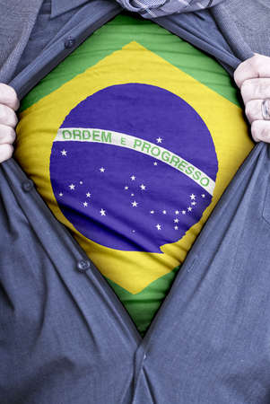 A Brazilian businessman rips open his shirt and shows how patriotic he is by revealing his countries flag beneath printed on a t-shirt Stock Photo - 12991153