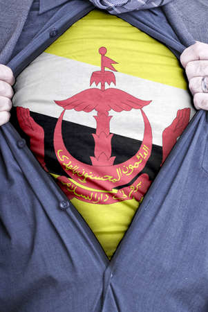 A Bruneian businessman rips open his shirt and shows how patriotic he is by revealing his countries flag beneath printed on a t-shirt Stock Photo - 12991170