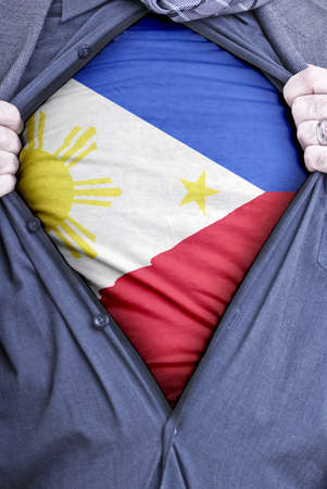 A Filipino businessman rips open his shirt and shows how patriotic he is by revealing his countries flag beneath printed on a t-shirt photo
