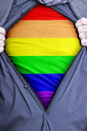 gay flag: A Gay businessman rips open his shirt and shows how proud he is to be gay by revealing the rainbow flag beneath printed on a t-shirt Stock Photo