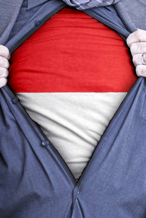 nationalism: An Indonesian businessman rips open his shirt and shows how patriotic he is by revealing his countries flag beneath printed on a t-shirt