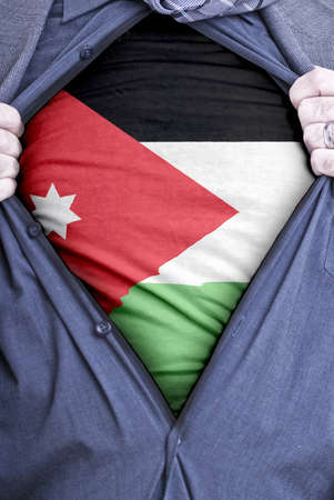 A Jordanian businessman rips open his shirt and shows how patriotic he is by revealing his countries flag beneath printed on a t-shirt photo