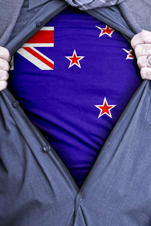 A Kiwi businessman rips open his shirt and shows how patriotic he is by revealing his countries flag beneath printed on a t-shirt photo