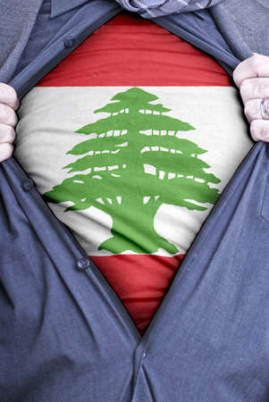 A Lebanese businessman rips open his shirt and shows how patriotic he is by revealing his countries flag beneath printed on a t-shirt photo