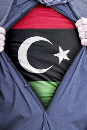 libyan: A Libyan businessman rips open his shirt and shows how patriotic he is by revealing his countries flag beneath printed on a t-shirt Stock Photo