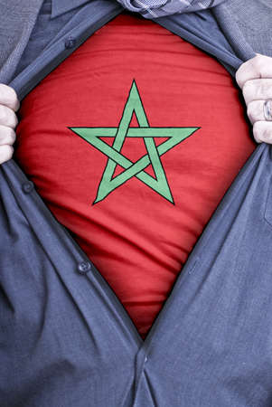 A Moroccan businessman rips open his shirt and shows how patriotic he is by revealing his countries flag beneath printed on a t-shirt Stock Photo - 12991102