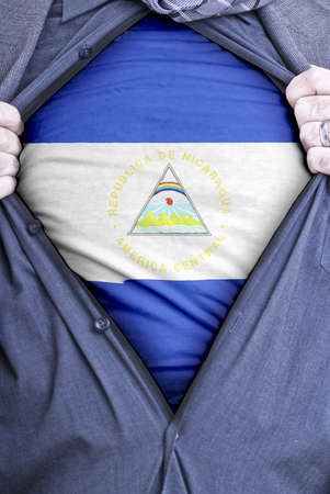 nicaraguan: A Nicaraguan businessman rips open his shirt and shows how patriotic he is by revealing his countries flag beneath printed on a t-shirt Stock Photo
