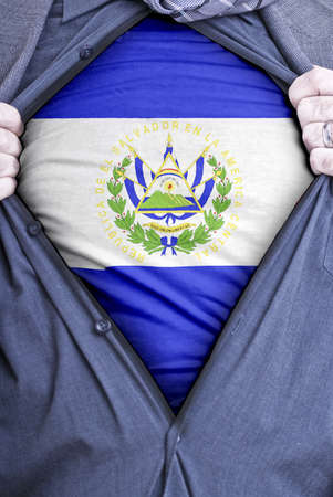 el: A Salvadoran businessman rips open his shirt and shows how patriotic he is by revealing his countries flag beneath printed on a t-shirt Stock Photo