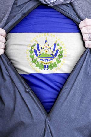 bandera de el salvador: Un empresario salvadoreño arranca abrir su camisa y muestra cómo patriótica que es mediante la revelación de su bandera por debajo de países impreso en una camiseta Foto de archivo