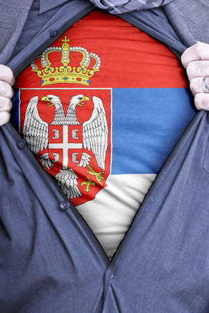 A Serbian businessman rips open his shirt and shows how patriotic he is by revealing his countries flag beneath printed on a t-shirt photo