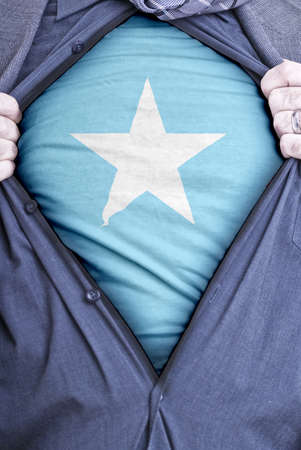 somali: A Somali businessman rips open his shirt and shows how patriotic he is by revealing his countries flag beneath printed on a t-shirt