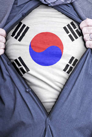 A South Korean businessman rips open his shirt and shows how pattic he is by revealing his countries flag beneath printed on a t-shirt Stock Photo - 12991118