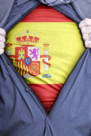 A Spanish businessman rips open his shirt and shows how patriotic he is by revealing his countries flag beneath printed on a t-shirt photo