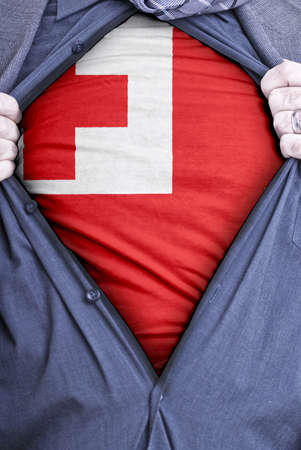 A Tongan businessman rips open his shirt and shows how patriotic he is by revealing his countries flag beneath printed on a t-shirt Stock Photo