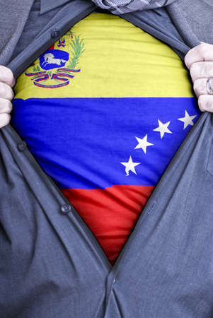 A Venezuelan businessman rips open his shirt and shows how patriotic he is by revealing his countries flag beneath printed on a t-shirt photo